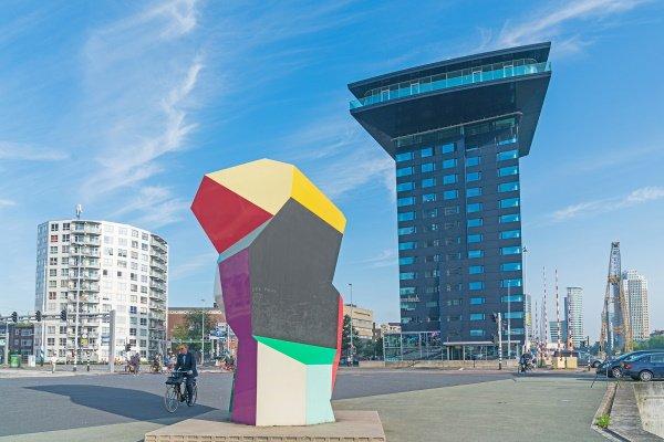 Voorzijde van Intell Hotel met een kunstwerk op de voorgrond